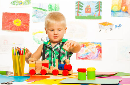 Portrait of 2 years old blond boy in the preschool art class  with pencils toys and blocks photo