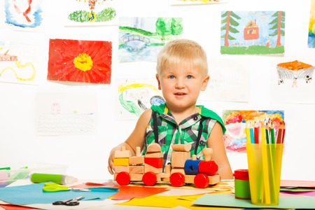 2 years old happy boy in the preschool art class  with pencils toys and blocks photo