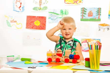2 years old blond boy in the preschool art class  with pencils toys and blocks photo
