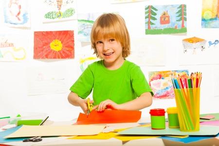 Cortar y lección de pegamento con 4 años de edad chico rubio con unas tijeras y una sonrisa Foto de archivo - 26599643