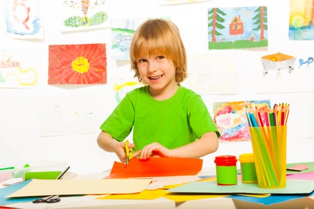 Cut and glue lesson with 4 years old blond boy with scissors and smile Stock Photo
