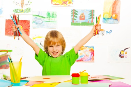 lifted hands: Happy blond boy holding color pencils and lifting hands