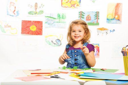 gluing: Little 3 years old blond girl gluing color cardboard smiling and looking at camera