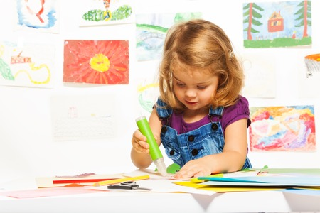 gluing: Little 3 years old blond girl gluing color cardboard with glue stick Stock Photo