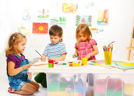 gluing: Kindergarten kids by the table gluing and painting on creative art class Stock Photo
