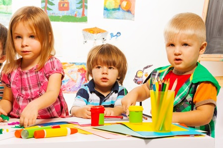 Little kids on painting class sitting together with pencils and paints