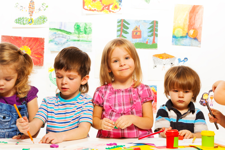 Group of little kids on painting class sitting together with pencils and paints photo