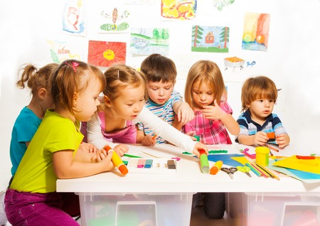 Large group of little kids on painting class sitting together with pencils and paints
