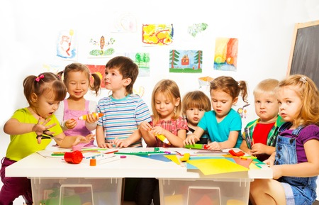Large group of little kids painting with pencils and gluing with glue stick on art class in kindergarten