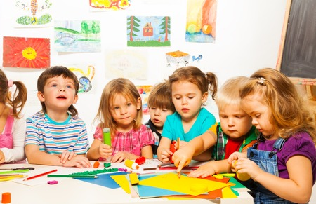 preschool: Group of little kids painting with pencils and gluing with glue stick on art class in kindergarten Stock Photo