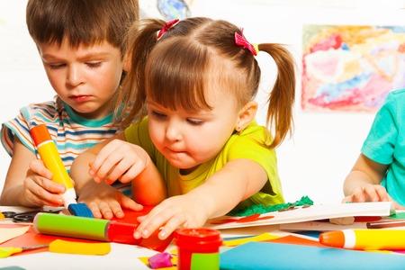 Twee kleine kinderen knutselen met schilderkunst en blauwen tools op creatieve schoolklas Stockfoto