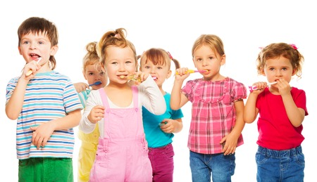 Three happy little 3-4 years old kids group standing with toothpaste