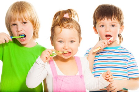 Three happy little 3-4 years old kids standing with toothpaste