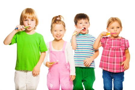 Close shoot of four happy little 3-4 years old kids standing with toothpaste Stock Photo