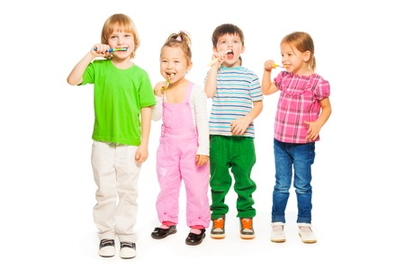 Four happy little 3-4 years old kids standing with toothpaste Stock Photo