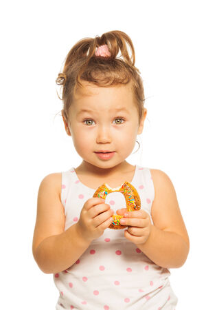 hungry kid: Close portrait of Asian girl with ponytails with donut  Stock Photo