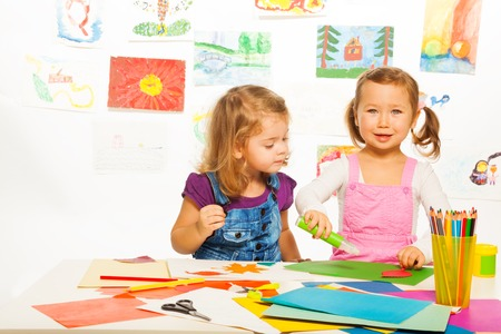 gluing: Two beautiful 3-4 years old girls cutting and gluing color cardboard
