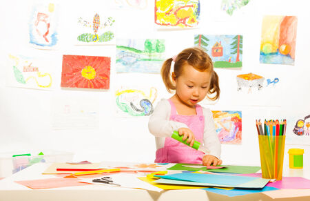 Little Asian girl gluing and making crafts with color cardboard paper