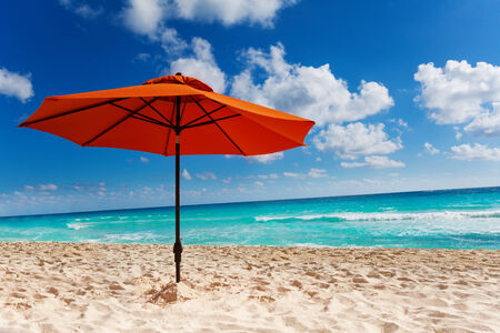 deserted: Beautiful orange umbrella on the white sand beach with clean ocean