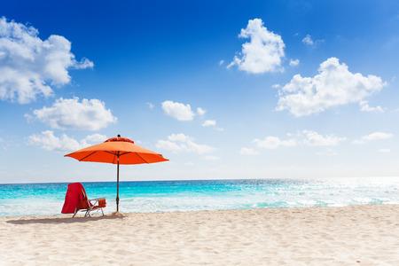 Oranje paraplu op het schone mooie strand en de zee panorama met blauwe hemel met een paar witte wolken Stockfoto