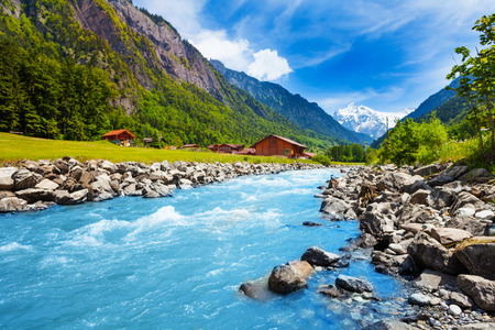 Breathtaking Swiss landscape with river stream, rocks and houses with Alps background  in a sunny summer day Standard-Bild