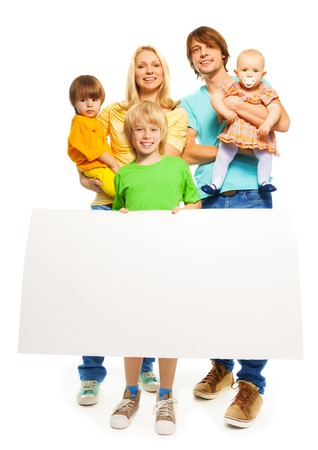 Portrait of a family standing isolated on white, mother, father, little boys and baby girl holding blank advertising banner