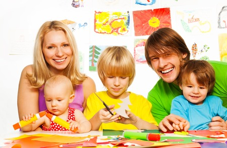All family crafting with paper glue and scissors, mom, dad and three kids Stock Photo