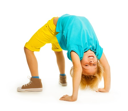 Happy 8 years old boy standing in acrobatic pose upside down on hands  photo