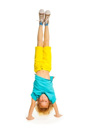 upside: 8 years old boy standing on hands upside down isolated on white  Stock Photo