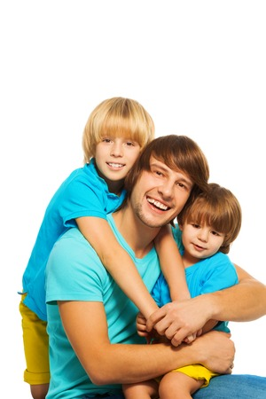 Happy laughing father sitting isolated on white with two young sons