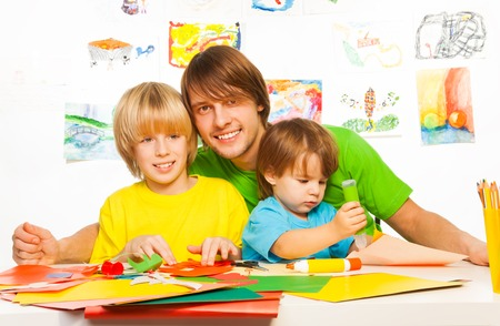 Happy dad with little kids cutting and gluing paper together with big smile on faces Reklamní fotografie