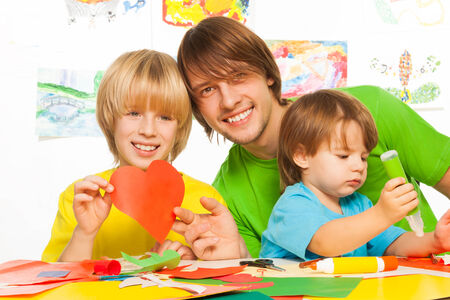 gluing: Father and little boys cutting and gluing heart shapes out of paper as they learn to craft