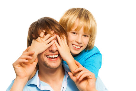 Young happy smiling father guesses who with his son cover face with palms