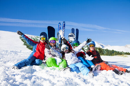 ski goggles: Five happy friends sitting on the snow lifting hands up with snowboards and skis wearing goggles on the mountains background