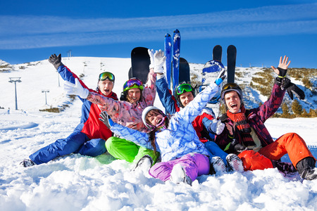ski goggles: Five happy friends sitting with snowboards and skis on the snow lifting hands up in the air on the mountains background