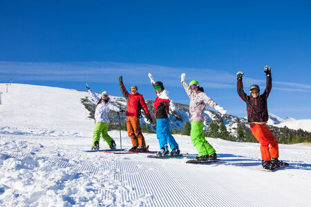One skier and 4 snowboarders wearing ski mask standing in a row and lifting hands up in the air and making fun on the mountains background photo