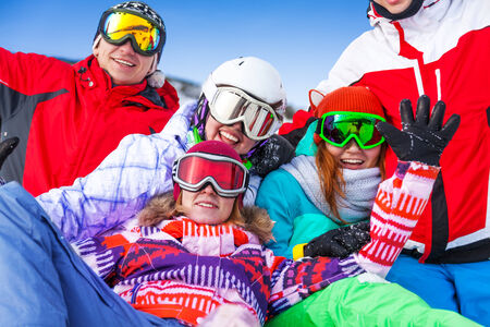 Group of smiling happy snowboarders having fun very close to each other photo