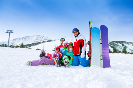 Group of five happy smiling snowboarders with snowboards and skis in the mountains photo