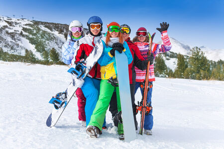 Group of happy smiling 2 men and 3 women with snowboards and skis standing on the mountains background photo