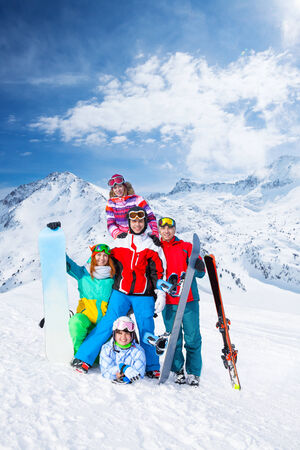 ski goggles: Group of happy excited smiling 2 men and 3 women with snowboards and skis wearing goggles standing and posing on the mountains background