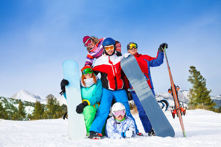 Group of happy excited smiling mates of 2 men and 3 women with snowboards and skis wearing goggles standing and posing on the mountains background photo