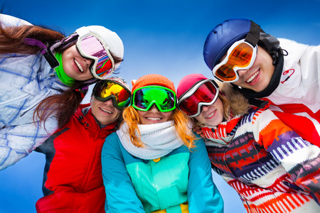 ski mask: Happy smiling friends of 4 women and 1 man posing in half circle with ski mask