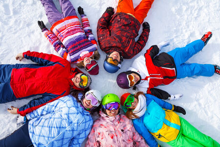Seven cheerful happy friends in snowboards costumes lying in a circle on the snow wearing goggles photo