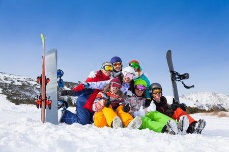 ski goggles: Seven friends with positive mood wearing goggles sitting with snowboards and skis the mountains background