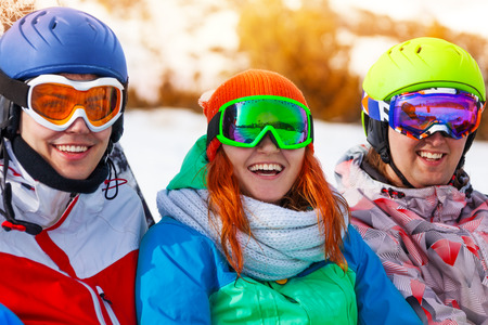 ski mask: Portrait of three friends, 1 woman and 2 men  wearing goggles sitting on the ground on mountains background Stock Photo
