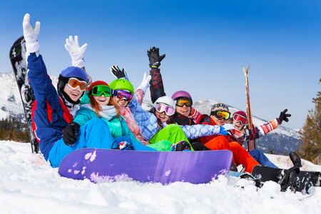 ski mask: Seven happy smiling friends wearing ski mask sitting together lifting hands up in the air on the mountains background Stock Photo