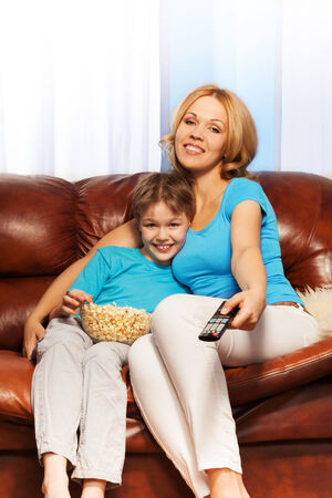 Happy mother with remote control and her son are watching television with popcorn sitting on the sofa at home photo