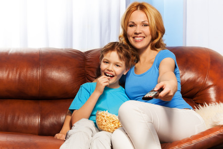 Smiling mother uses remote control and son together are watching television with popcorn sitting on brown leather sofa at home photo