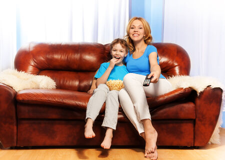 Happy mother with remote control and her son are watching television with popcorn sitting on brown leather sofa at home photo