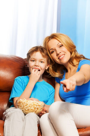 Happy mother pointing forward and son eating popcorn are watching together TV while sitting on the brown sofa at home photo